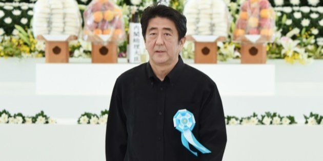 Japanese Prime Minister Shinzo Abe returns his seat after offering a flower at an altar during a memorial...