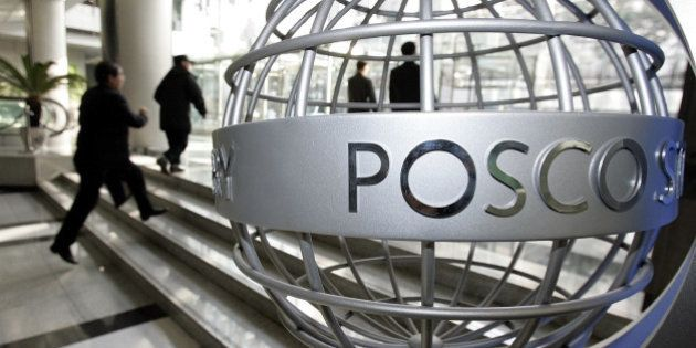 Visitors walk past a sculpture displaying the Posco logo at the company's headquarters in Seoul, South...