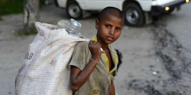 A young Indian ragpicker looka on as he collects used mineral water bottles in Siliguri on June 12, 2013,...