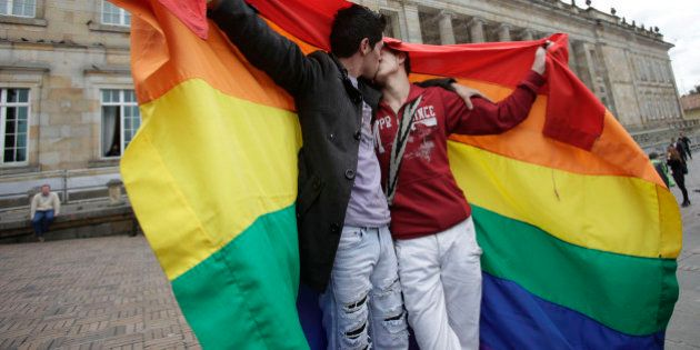 LGBT activists kiss in front of Colombia's Congress building to show support for a proposed bill to legalize...