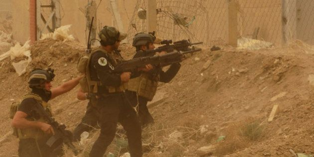 Security forces defend their headquarters against attacks by Islamic State extremists during sand storm...
