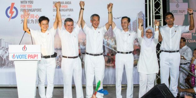 Lee Hsien Loong, Singapore's prime minister and leader of the People's Action Party (PAP), center, gestures...