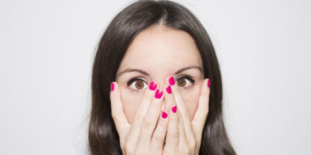 Close-up portrait. Surprise, fear and horror.Woman covering her face with two hands hand and looking...