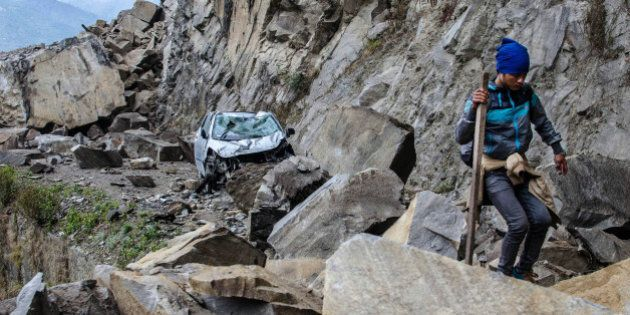 In this Monday, April 27, 2015 photo, a Nepalese man walks over fallen rocks and past a crushed car on...