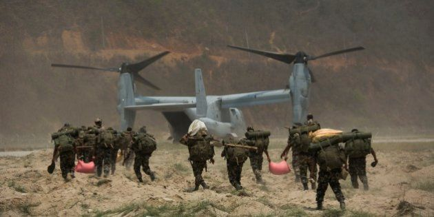 Nepalese soldiers prepare to board one of U.S. Ospreys which is used to deploy them in the quake affected...