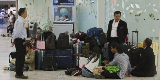 Thai passengers of Mexicana airlines wait for information at the international airport in Mexico City,...