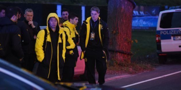 Police escort Dortmund's players after the team bus of Borussia Dortmund had some windows broken by an...