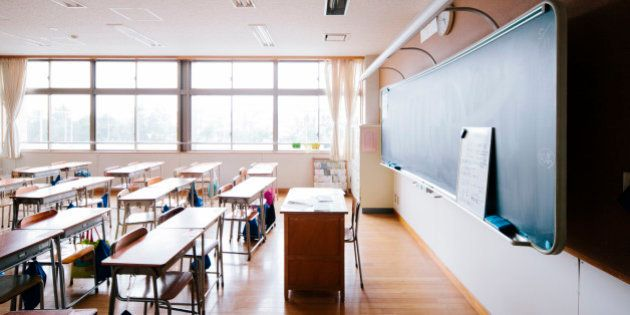 A view of a Japanese school classroom, traditional wooden desks and chairs, and blackboard. Interior...