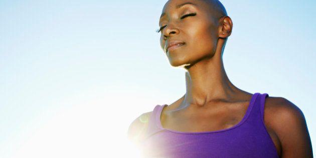 African American woman smiling in sunburst under blue sky