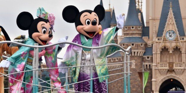 Disney characters Mickey (R) and Minnie Mouse (L), dressed in traditional Japanese kimonos, wave to greet...