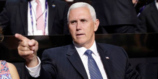 Vice Presidential nominee Gov. Mike Pence of Indiana points as he sits during the second day session...