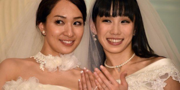 Japanese actress Akane Sugimori (R) and her partner Ayaka Ichinose, both dressed in white, display their...