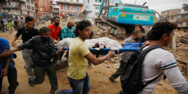 Volunteers carry the body of a victim on a stretcher, recovered from the debris of a building that collapsed...