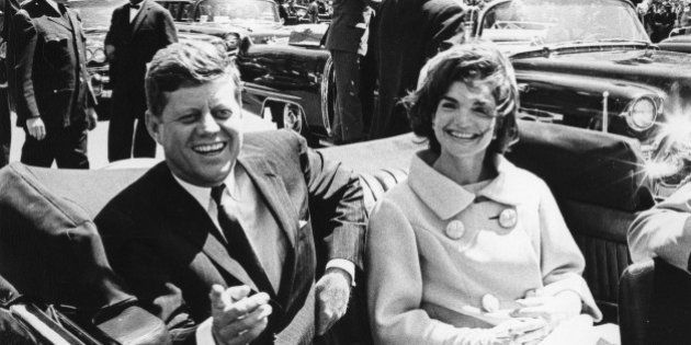 Former United States President John F. Kennedy and first lady Jackie Kennedy sit in a car in front of...