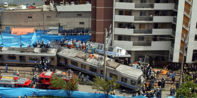 AMAGASAKI, JAPAN - APRIL 25: Rescue workers attempt to free trapped passengers from a crushed commuter...