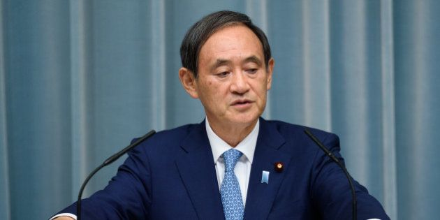 Yoshihide Suga, chief cabinet secretary of Japan, listens during a press conference at the official residence...