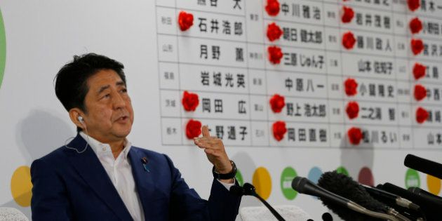Japan's Prime Minister Shinzo Abe, leader of the Liberal Democratic Party, answers a question from reporter...