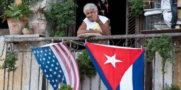 A Cuban gives the thumbs up from his balcony decorated with the US and Cuban flags in Havana, on January...