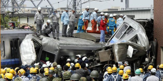 AMAGASAKI, JAPAN: Rescue workers and self defence force soldiers search for injured passengers from a...