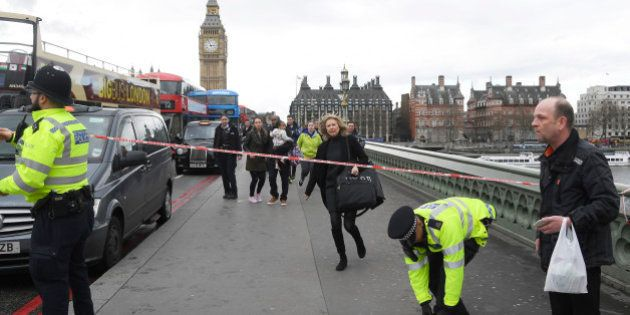 A woman ducks under a police tape after an incident on Westminster Bridge in London, March 22, 2017....