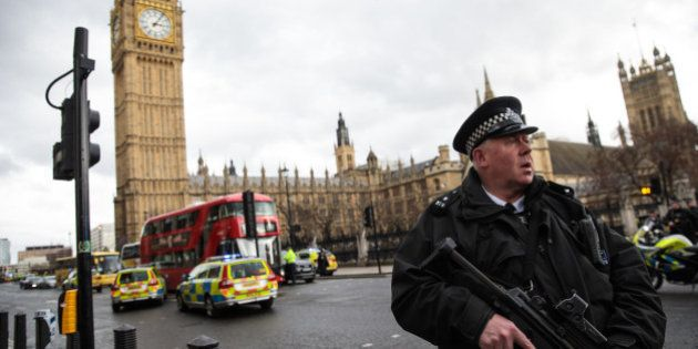 LONDON, ENGLAND - MARCH 22: An armed police officer stands guard near Westminster Bridge and the Houses...
