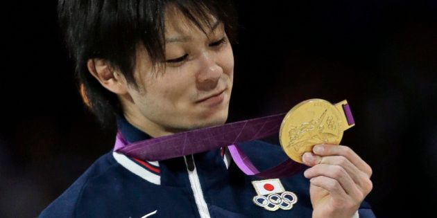 Japanese gymnast Kohei Uchimura holds his gold medal during the medal ceremony of the Artistic Gymnastic...