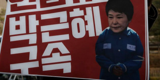 A protester demanding arrest warrant of ousted South Korean President Park Geun-hye holds a photograph...