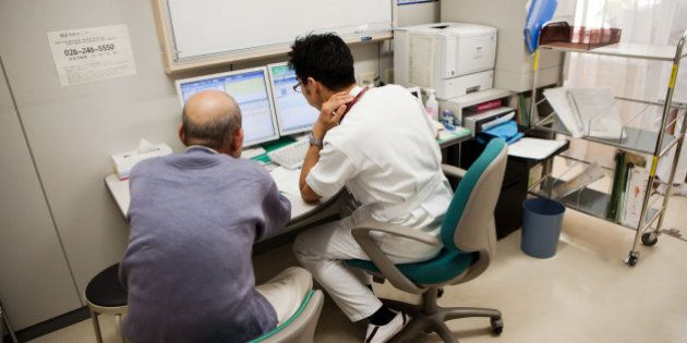 Kojiro Tokutake, a gastroenterologist at Nagano Prefectural Suzaka Hospital, right, discusses diagnostic...
