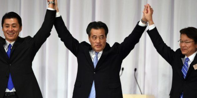 Newly elected opposition Democratic Party of Japan (DPJ) leader Katsuya Okada (C) raises his arms with...