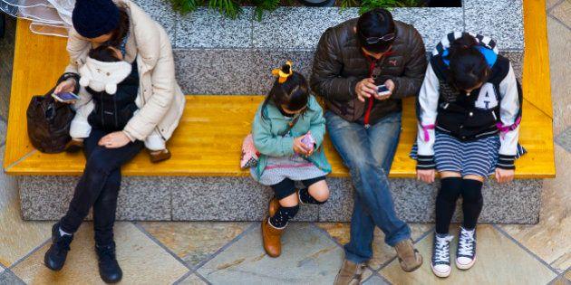 Kawasaki, Kanagawa Prefecture, Japan - March 8, 2015: People sitting on bench in a shopping mall are...