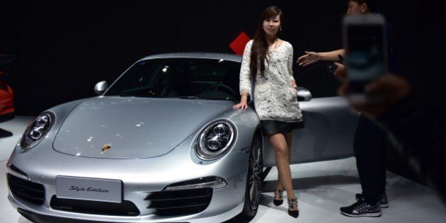 A woman poses next to a Porsche 911 Carrera Style Edition at the 16th Shanghai International Automobile...