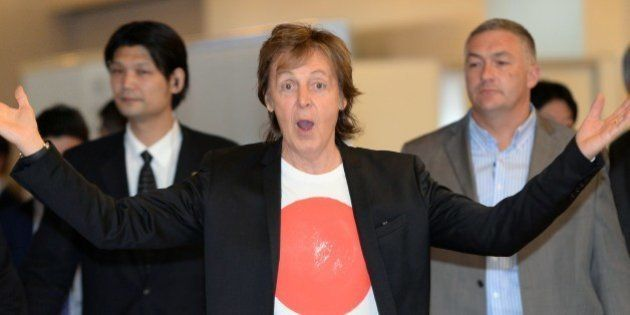 Paul McCartney greets fans and journalists upon his arrival at the Haneda airport in Tokyo on May 15,...