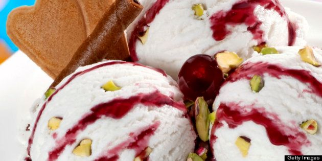 Vanilla ice cream balls with cherry syrup and pieces of