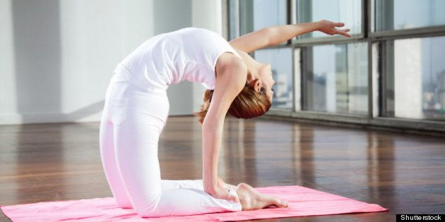 Full length of a young woman practicing yoga in Camel position on