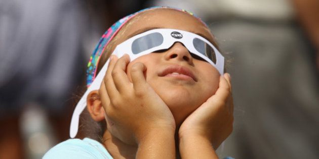 GARDEN CITY, NY - AUGUST 21: A spectator looks skyward during a partial eclipse of the sun on August...