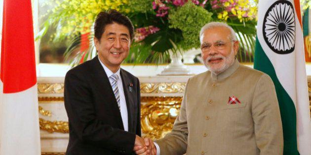 India's Prime Minister Narendra Modi, right, and Japan's Prime Minister Shinzo Abe shake hands before...