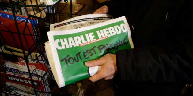 A seller of newspapers installs in shelf, several Charlie Hebdo newspapers at a newsstand in Nice southeastern...