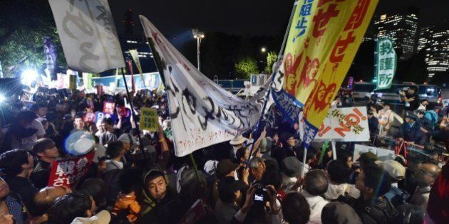 Demonstrators hold placards during a protest against Prime Minister Shinzo Abe's controversial security...
