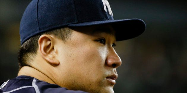 New York Yankees starting pitcher Masahiro Tanaka, of Japan, watches his team play during the ninth inning...