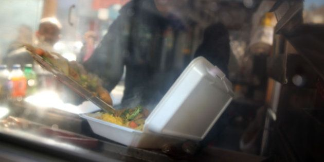 NEW YORK, NY - DECEMBER 19: A food cart worker fills a styrofoam take-out container with food for a customer...