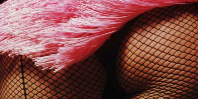 Burlesque performer's buttocks in fishnet stockings,