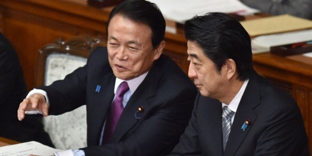 Japanese Finance Minister Taro Aso (L) speaks with Prime Minister Shinzo Abe (R) during a session at...