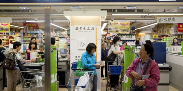 Shoppers exit a ParknShop supermarket, operated by Hutchison Whampoa Ltd., at Lok Fu Plaza, operated...