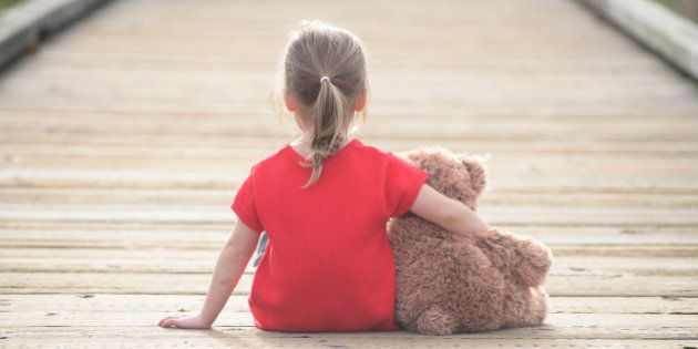 Little girl in a red dress waiting on a boardwalk hugging teddybear, view from