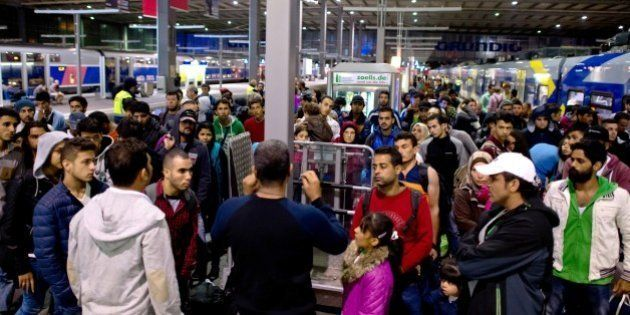 Refugees and migrants arrive at the central station in Munich, southern Germany Sunday Sept. 13, 2015....