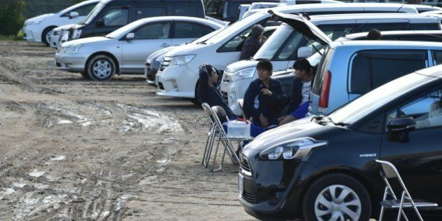 Earthquake-affected evacuees rest near their vehicles at a temporary parking lot in Mashiki, Kumamoto...