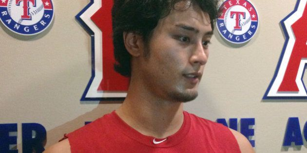 Texas Rangers' Yu Darvish, of Japan, talks with reporters outside the clubhouse before the Rangers' baseball...