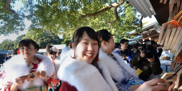 Twenty-year-old female tour guides dressed in traditional kimonos hang up 'ema', or voting tablets, with...