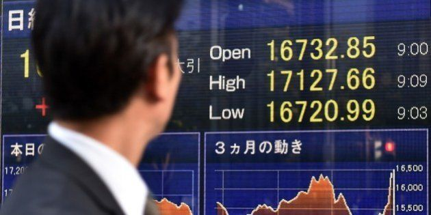 A pedestrian looks at a stock market share prices board in Tokyo on November 4, 2014. Tokyo's Nikkei...