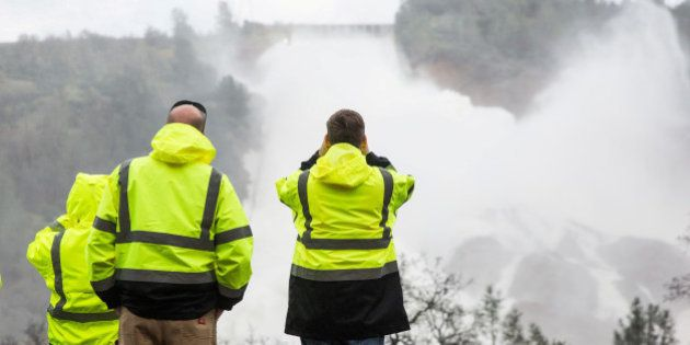 California Department of Water Resources personnel monitor water flowing through a damaged spillway on...